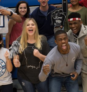 Augusta University students cheer at a basketball game.