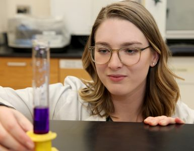 Kayla Ward, chemistry major, looks at vile of purple liquid