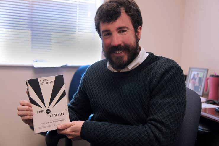 Professor Adam Diehl with his copy of Crime and Punishment by Fyodor Dostoevsky.