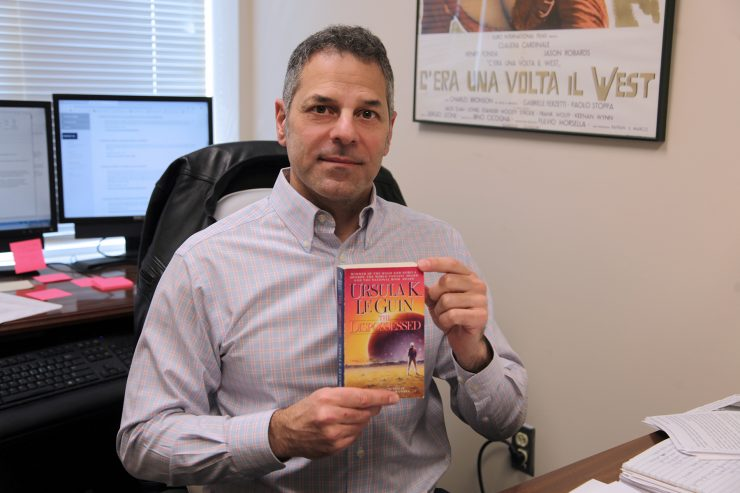 Professor Todd Hoffman holds up his copy of Ursula LeGuin's The Dispossessed