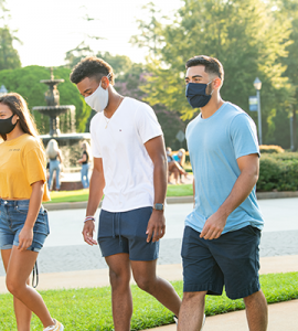 One female and two male students wearing masks walking on campus