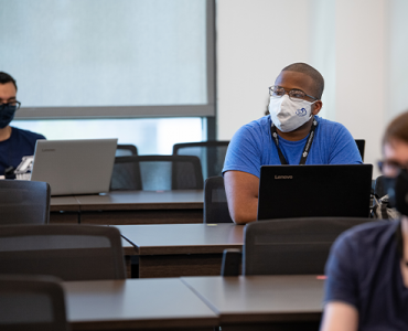 Students wearing a mask sitting in a cybersecurity classroom