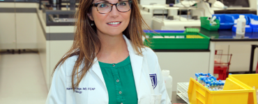 Female physician smiling in science lab